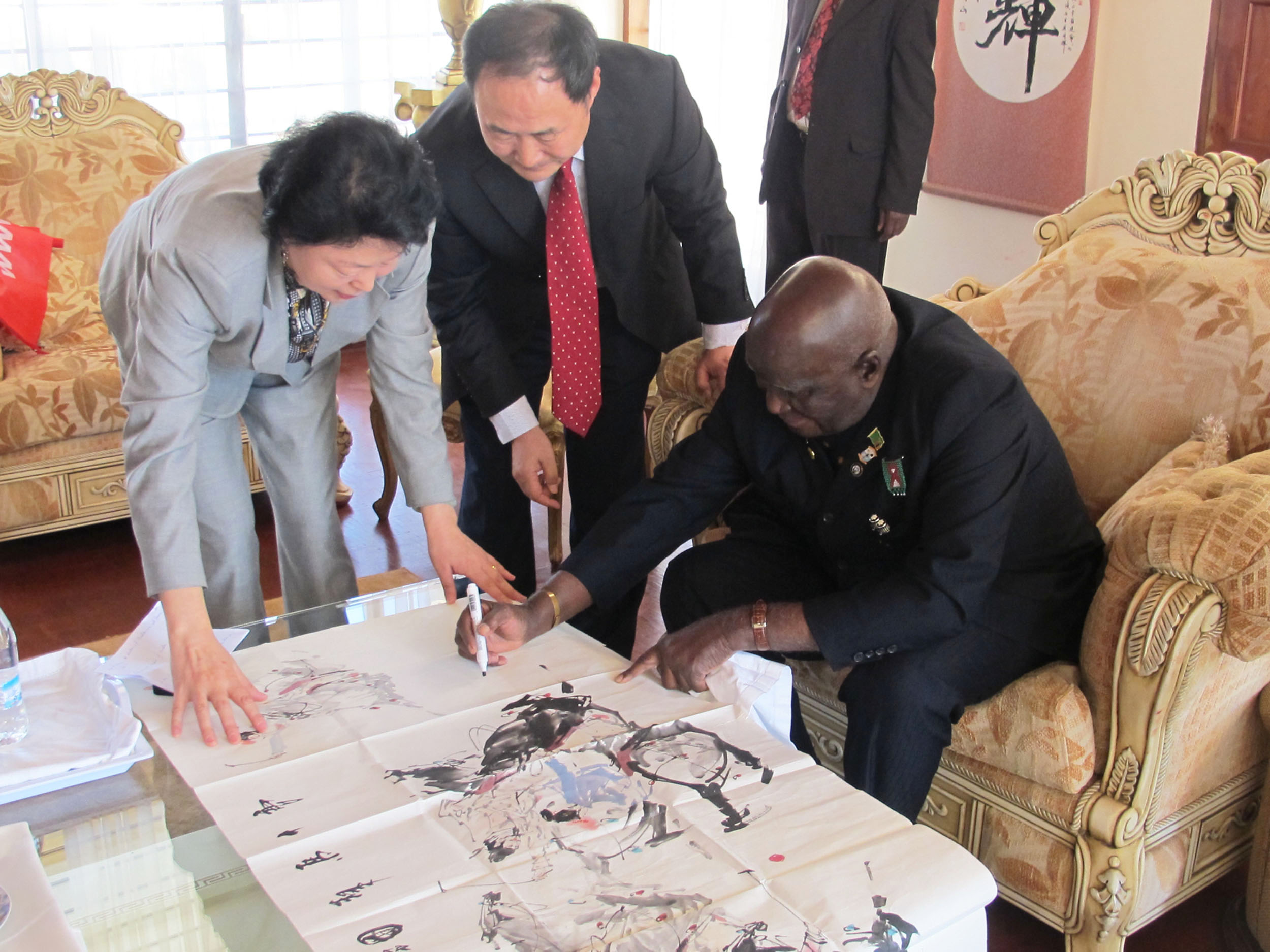 Kaunda, the former president of Zambia, signing his name on a painting